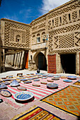 Building and plates and rugs on display in a small square, Tozeur, Tunisia