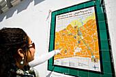 Female tourist looking at Medina map on wall, Tunis, Tunisia