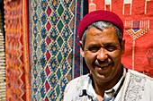 Souvenir shop keeper by carpets, Medina, Tozeur, Tunisia, North Africa