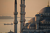 Ship sailing along the Bosphorus behind the Sultanahmet or Blue mosque at dawn, Istanbul, Turkey.