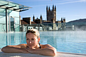 Young woman relaxing in roof top pool, Thermae Bath Spa, Bath, England