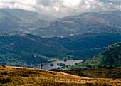 Hiker looking at view at Rydal Water, Lake District, England, UK