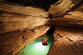 Speleology, caving, caver on a boat on an underground river, Event de Brun (Gard, France)