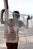 Sénégal, Abene, Young Gambian woman holding a hammoc