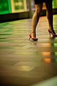 Woman's legs walking in the street, heel shoes