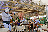 France, Var, Riviera, Ramatuelle, Pampelonne beaches. Couple being photographied at a restaurant.