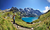 Woman looking over Oeschinen Lake to mountain scenery, UNESCO World Heritage Site Jungfrau-Aletsch protected area, Bernese Oberland, canton of Bern, Switzerland