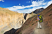 Woman with backpack looking over a gorge, Snertse, Zanskar Range Traverse, Zanskar Range, Zanskar, Ladakh, Jammu and Kashmir, India