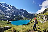 Woman looking over Oeschinen Lake, Bluemlisalp, UNESCO World Heritage Site Jungfrau-Aletsch protected area, Bernese Oberland, canton of Bern, Switzerland