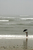 Young Woman Standing in Surf With Umbrella in Fog