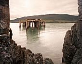 Old Fishing Pier Viewed Though Sea Wall Opening, Juneau, Alaska, USA