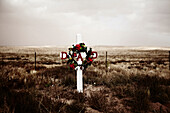 Cross and Wreath of Flowers at Gravesite in Arid Field, Arizona, USA