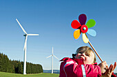Little girl with toy windmill, wind turbine in the background, Black Forest, Baden-Wurttemberg, Germany