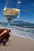 Hand holding up a glass of white wine at Bloubergstrand with Table Mountain in background, Western Cape, South Africa, RSA, Africa