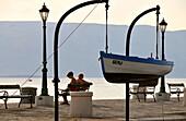 Two women sitting on a bench in the harbour of Senji, near Velebit, Adriatic coast, Croatia