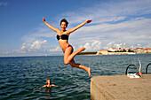 Woman jumping into the water, Beach at Rab, Rab Island, Kvarnen Gulf, Croatia