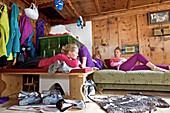 Three young women relaxing in a cosy alpine hut after skiing, See, Tyrol, Austria