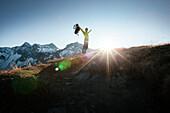 Hiker on the summit of Mottakopf, Schesaplana in the background, Brandner Valley, Vorarlberg, Austria