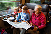Two girls, a young and an older woman are sitting in a train, Switzerland.