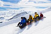 Two men, a woman and a girl tobogganing on the toboggan run at the ski resort Stoos, Kanton Schwyz, Switzerland