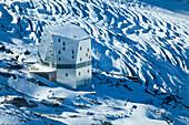 Aerial view of an alpine hut in the mountains, the New Monte Rosa-Hut with Grenzgletscher glacier in the background, Zermatt, Valais, Switzerland