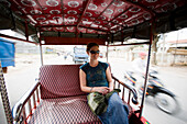 Young woman riding in tuk-tuk in Phnom Penh, Cambodia, Phnom Penh, Cambodia.