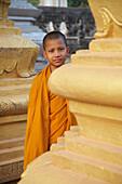 Portrait of young monk between pillars, Wat Bo Temple, Siem Reap, Cambodia