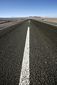 Dividing line on empty, paved road, Low Angle View, Road between Chile and Argentina, Andes, San Pedro de Atacama, Chile
