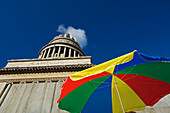 View from below of the dome of the Capitolio in Havana with rainbow umbrella in the foreground, Cuba.