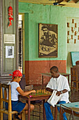 Locals playing chess at a chess club, with a poster of Che Guevara in the background, Santiago de Cuba, Cuba