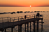 A silhouetted couple watch the sun setting out at sea, Cyprus