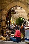 Woman reading guidebook beside stalls, Khan El Khalili, Cairo, Egypt