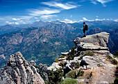 Walker admiring the view from the top of Capo d'Orto, Corsica, Capo d'Orto near Porto, Corsica, France