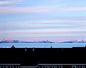 View over rooftop towards coastline and mountains, Uummannaq Island, Greenland