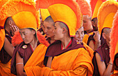Nuns / monks in traditional dress with yellow orange hats and robes praying at 800 year old birthday celebration / rituals of the Buddhist Drukpa Lineage, Naro Photang Shey, (Shey Monastery), Leh Ladakh, Indian Himalayas, India