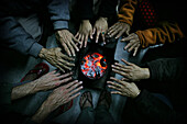 People warming their hands over a sikri, Close Up, Lunglei, Mizoram, North East states, India.  A sikri is a Mizo charcoal burner.