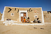 Two women siting in front of decorated mud hut, Jaisalmer, Rajasthan, India