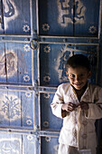 A young boy standing in front of a decorated julaha door in Jodpur, Rajasthan, India