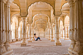 Tourist sitting in columned hallway in the  Amber Fort, Jaipur, Rajasthan, India