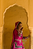 Laughing woman in traditional Rajasthani sari and jewellery in archway of old building, Jaipur, Rajasthan, India