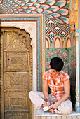 Woman writing postcard in decorated entrance area of the City Palace, Jaipur, Rajasthan, India