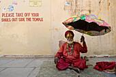 Sadhu with umbrella outside small temple, Jaipur, Rajasthan, India