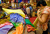 Woman being shown fabrics by salesman in a shop, Jaipur, Rajasthan, India