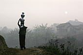Bru tribeswoman carrying water pots on her head at sunrise, Tripura, North East States, India . The Bru Tribe is also known as the Reang tribe.