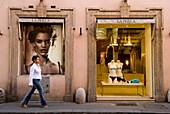 Woman walking past La Perla shop, Via Conotti, Rome, Italy