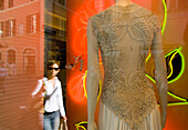 Window display of Valentino shop with reflection of woman, Via Condotti, Rome, Italy