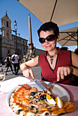 Woman eating pizza in the Piazza San Navona, Rome, Italy