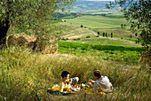 Couple having picnic beside olive trees looking over the countryside, Tuscany, Italy