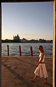 Woman walking along lagoon, Venice, Venice, Italy