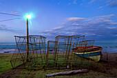 Lobster pots at the coast, Lobster pots beside fishing boat at dawn, Treasure Beach, Jamaica.